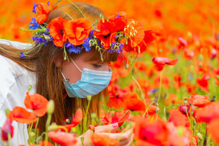 Portrait of young beautiful redhead woman in a mask with a poppy wreath on her head sniffing a flower on sunny summer day