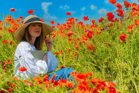 Young beautiful woman with laptop in poppy field in summer. Sitting on the ground. Remote work concept 版權商用圖片