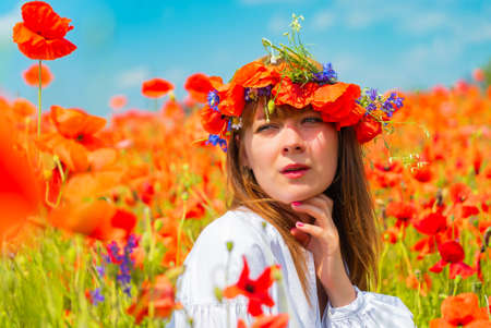 Portrait of young beautiful redhead woman with a poppy wreath on her head in a poppy field on sunny summer day 版權商用圖片