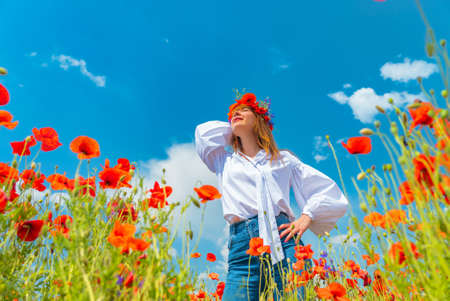 Young beautiful redhead woman in a white shirt with a poppy wreath on her head in a poppy field on sunny summer day