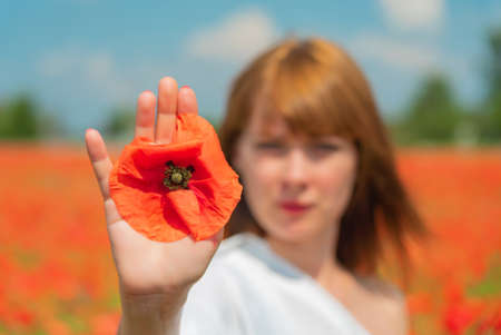 Young beautiful woman defocused holding a poppy flower in her hand