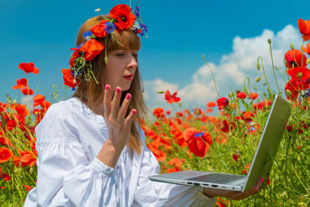 Young amazed woman working on a laptop in poppy field in summer. Sitting on the ground. Remote work concept