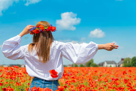 Young beautiful redhead woman in a white shirt with a poppy wreath on her head standing backwards in a poppy field on sunny summer day