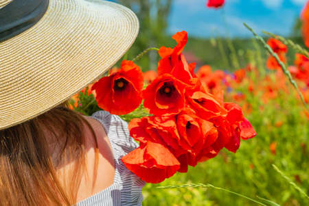 Young girl in the white dress and hat from tha back with a poppy flowers in the hand