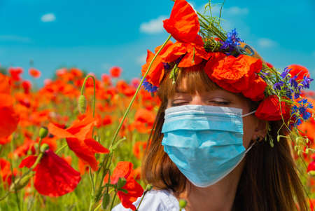 Portrait of young beautiful redhead woman in a mask with a poppy wreath on her head in a poppy field on sunny summer day