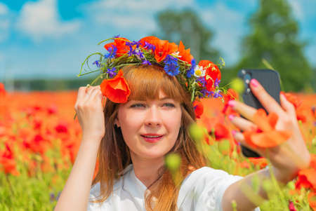 Young beautiful woman with a poppy wreath on the head taking selfie in the field on a summer day 版權商用圖片