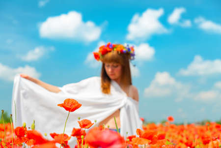 Defocused young beautiful redhead woman in a white shirt with a poppy wreath on her head in a poppy field on sunny summer day