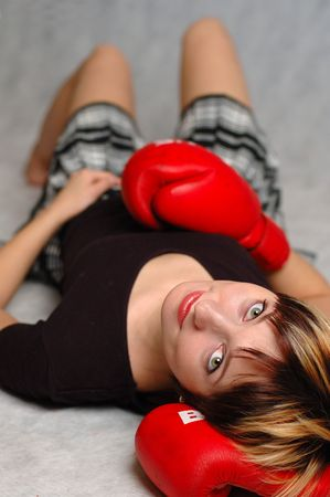 The girl in boxing gloves laying on a floor. photo