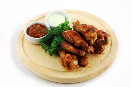 Chicken legs on a wooden support on a white background with sauce Stock Photo