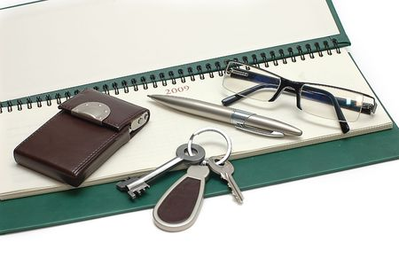 Diary, glasses and keys on a white background photo
