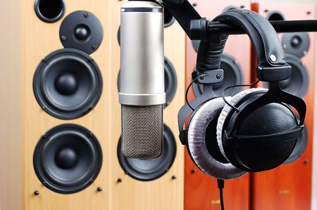 shure: Headphones and microphone in sound studio on a background of acoustic systems Stock Photo