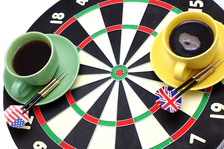 Game of a darts and coffee, in bright cups on a white background photo