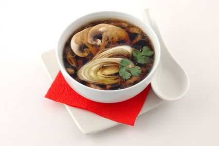 Fragrant hot soup with mushrooms in a white cup with a porcelain spoon