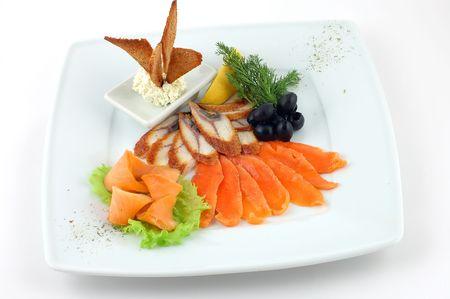 Plaque avec le poisson rouge et blanc avec des l�gumes sur un fond blanc