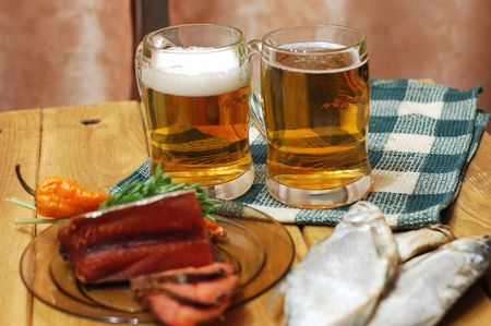 Mugs with beer and dried fishes photo