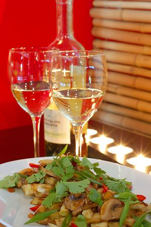White wine at restaurant with salad on a red background