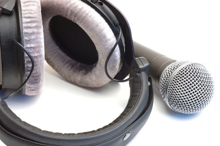 Modern scenic microphone and professional ear-phones on a white background