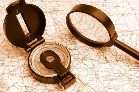 Compass and magnifier on a map for travel by close up photo