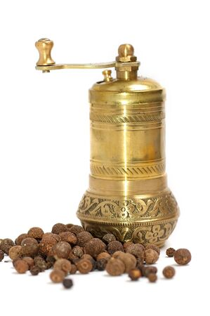 Black pepper with a mill close up on a white background photo