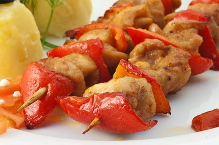 Shish kebab with tomatoes and a potato on a white dish close up