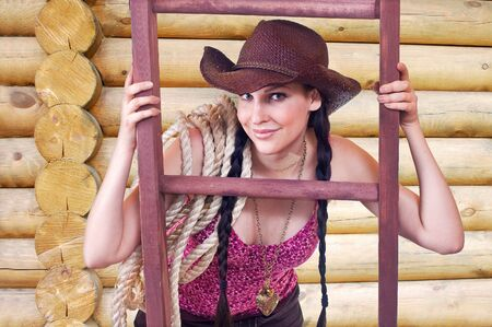 the cowgirl with a rope in a hat against a wooden wall photo