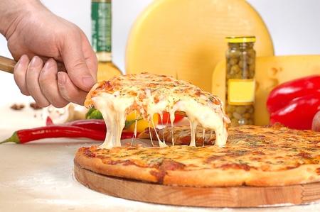 La pizza pr�par�e chaude avec du fromage collant sur une pelle de la cuisini�re Banque d'images