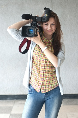 Portrait of the girl of the reporter with a videocamera with a direct sight