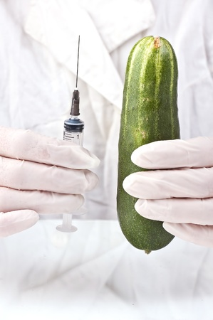 Cucumber and syringe in hands of the inspector on quarantine in a white dressing gown