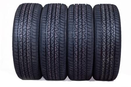 Le jeu complet de pneus neufs pour la voiture sur un fond blanc