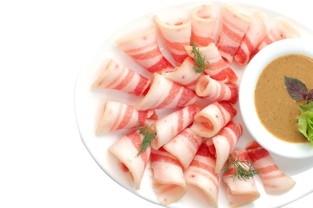 Bacon cut on a white dish with sauce and vegetables, the top view Stock Photo - 10783368