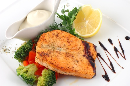 Salmon fried with spices with a lemon on a white plate with fennel Stock Photo - 11042464