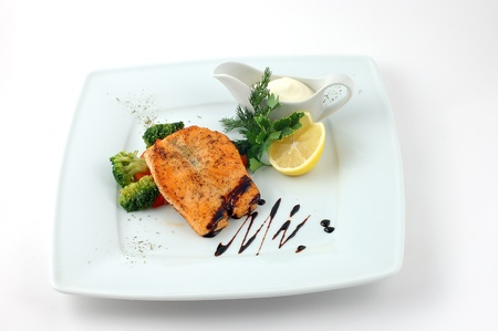 cholesterol free: Salmon fried with spices with a lemon on a white plate with fennel