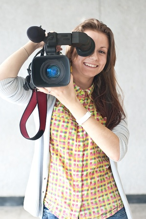 The woman the reporter with a videocamera directed to an objective of the photographer