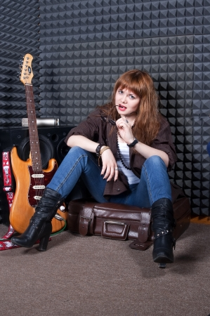 girl with a guitar in musical studio photo