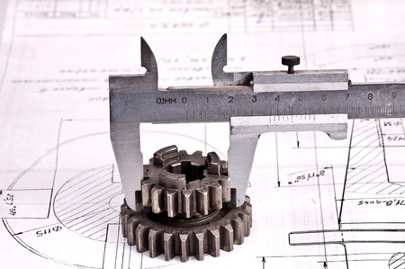 Close up of a calliper against the engineering project