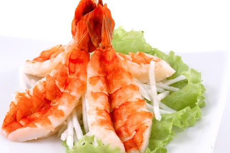 Shrimps with salad and vegetables on a white background close up Stock Photo