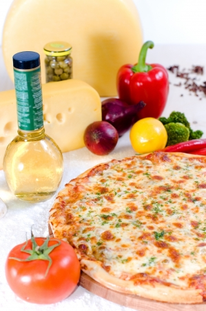 Pizza on a table with products close up at small depth of sharpness