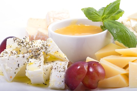 Collection of different cheese on a white dish with fruit and honey close up Stock Photo