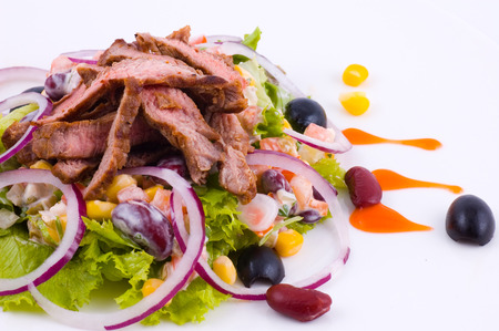 Meat with vegetables on a white dish close up Stock Photo