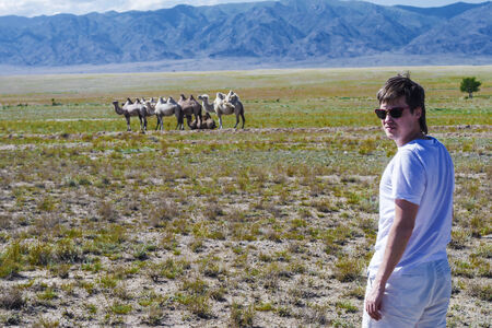 Portrait of the young man in steppe against mountains, the sky and camels
