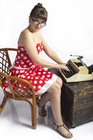The girl the secretary with a typewriter in a red dress on a white background photo