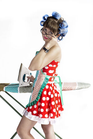 The girl the housewife with an iron in hair curlers and an apron on a white background