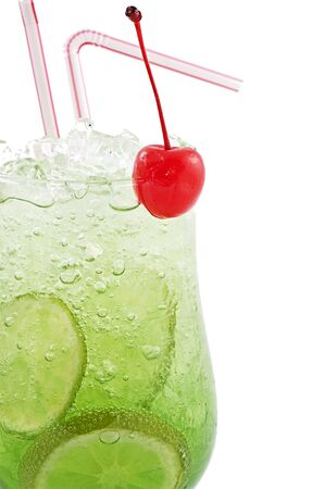 Green cocktail with a lemon and a cherry with ice and vials close up on a white background