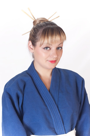 The lovely girl in a dark blue kimono and a traditional hat on a white background