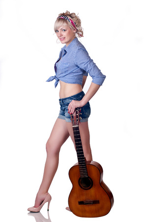 girl with a guitar in shoes on a high heel on a white background