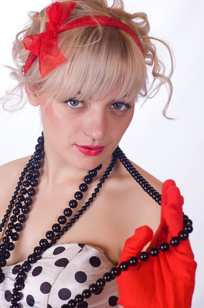 The girl the blonde in red gloves and a black beads a portrait close up