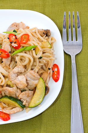 noodles cooked with vegetables on green background close-up Stock Photo