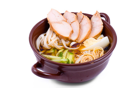 noodle soup with slices of meat in a brown dish on a white background