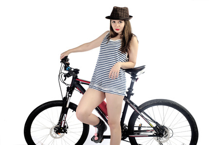The girl in a hat with a bicycle on a white background close up Stock Photo