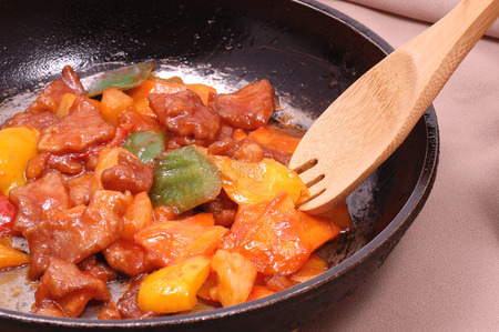 stew of vegetables and meat on a hot pan with a wooden spoon